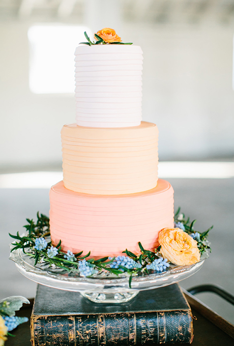 Cake by Baked Custom Cakes -Thin strips of fondant, in pastel shades of champagne, peach, and coral pink, are carefully wrapped around each tier to create a crisp, pleated look.