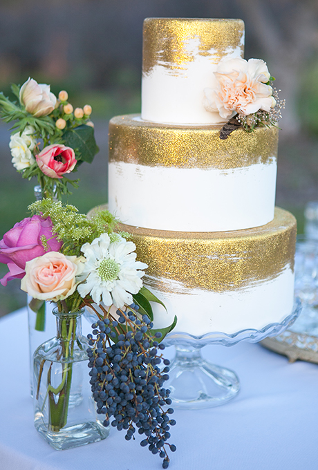 Gilded cake by Amber McKenney of Sweet on Cake, who applied gold disco dust (an edible glitter made for cake decorating) to the fondant-covered tiers, giving it a painterly brushstroke effect.