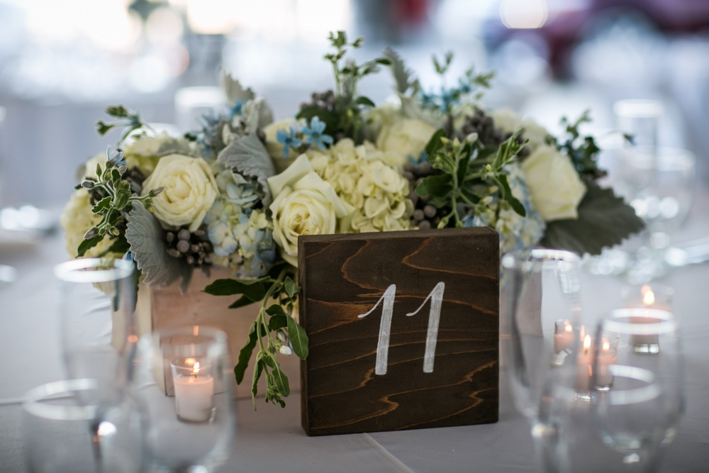 All white linens and chairs, set a clean and simple beachy look accented with rustic touches.Lily in the Valley created centerpieces of hydrangea and garden roses, of which echoed the shades blues in the couple's wedding invitations.