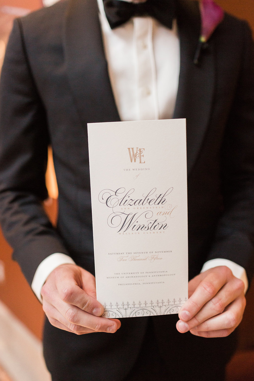 An usher holds program designed by Two Paper Dolls. The monogram and scroll motif were carried throughout all of their printed materials.